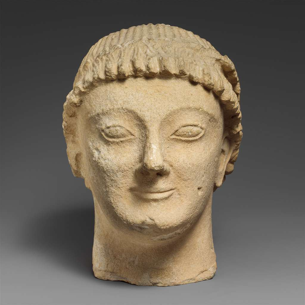 Limestone head of a beardless male votary with a wreath of rosettes